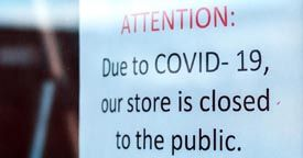 This is a picture of a sign on a business door that says closed to the public due to COVID-19 that symbolizes a business interruption lawyer.