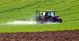 This is a picture of a tractor applying paraquat to a field of weeds that symbolizes a Paraquat Parkinson's attorney.